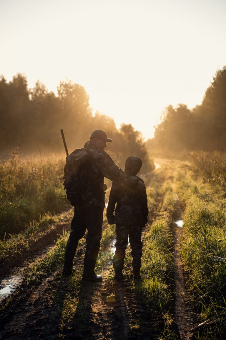 father pointing and guiding son on first deer hunt.